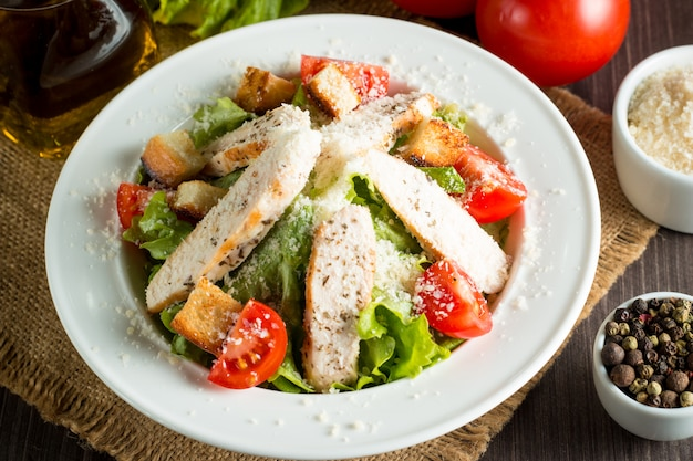 Fresh salad made of tomato, ruccola, chicken breast, eggs, arugula, crackers and spices. caesar salad in a white, transparent bowl on wooden background