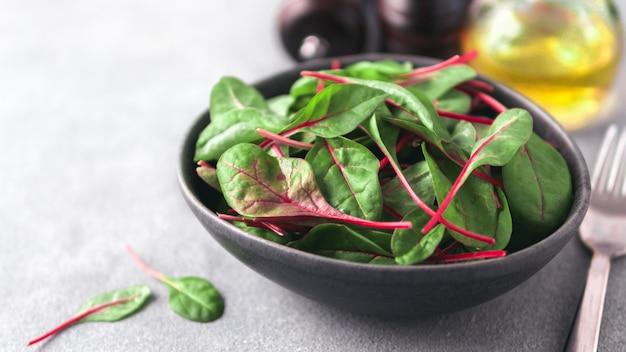 Свежий салат из листьев зеленого мангольда или мангольда свежие листья свеклы в керамической миске. скопируйте место для текста. баннер салата Premium Фотографии