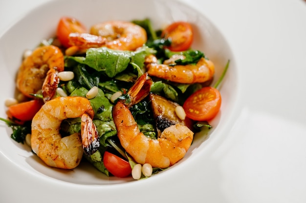 Fresh salad plate with shrimp, tomato and mixed greens on wooden surface close up
