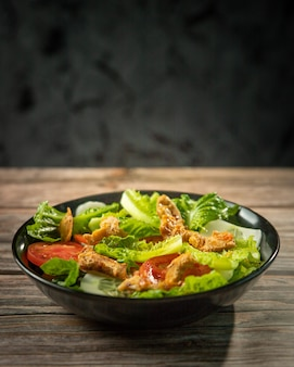 Fresh salad of romaine lettuce and tomatoes with roast chicken