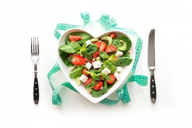 Fresh salad of strawberry, celery, spinach, cheese in plate as heart on white.