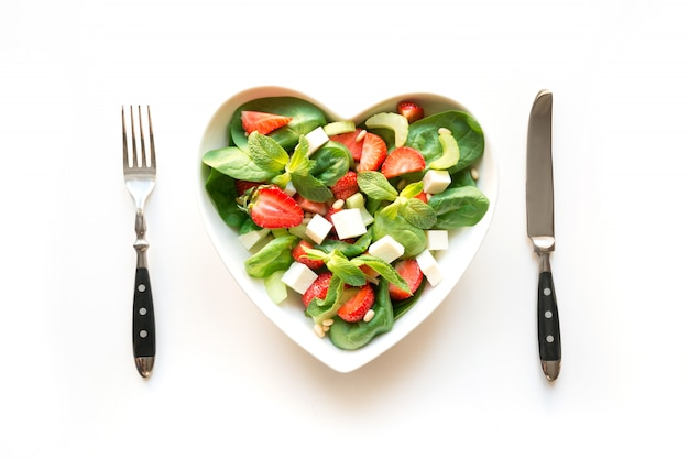 Fresh salad of strawberry, celery, spinach, pine nuts, cheese in plate as heart on white.