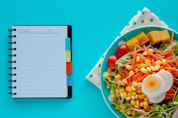 Fresh salad vegetable with boiled chicken egg and blank spiral notebook on blue background