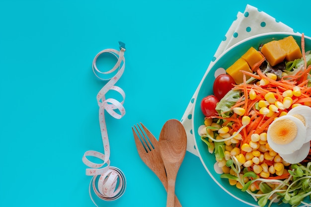 Fresh salad vegetable with boiled chicken egg, measuring tape, wooden spoon and fork on blue background