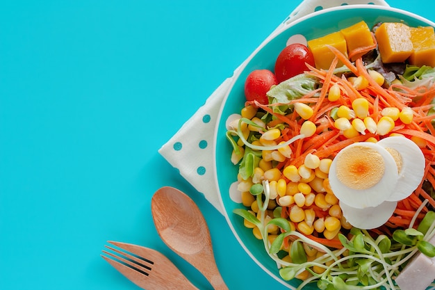 Fresh salad vegetable with boiled chicken egg, wooden spoon and fork on blue background