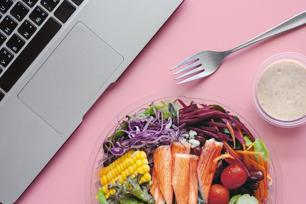 Свежие овощи салата с компьютерным ноутбуком на рабочем месте