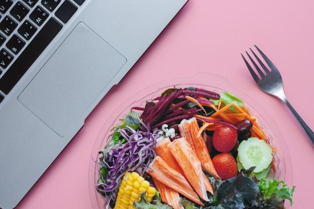 Салат из свежих овощей с компьютерным ноутбуком на рабочем месте