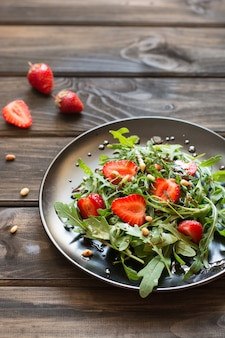 Fresh salad with arugula and strawbery with balsamic sauce and pine nuts. vegetarian food. salad with berries. vitamin food, diet salad on wooden background in black plate