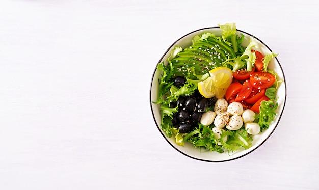 Fresh salad with avocado, tomato, olives and mozzarella in a bowl.