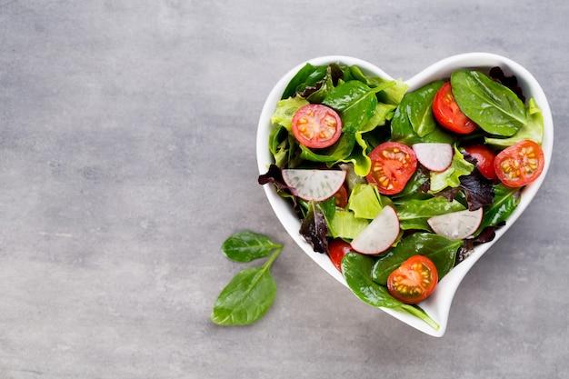 Свежий салат с молодым шпинатом и помидорами, редисом и салатом.