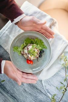 Свежий салат с говядиной, оливками, салатом и помидорами на синем на деревянном столе