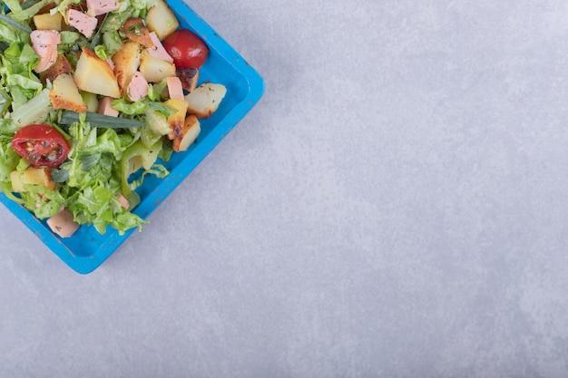 파란색 접시에 삶은 소시지와 신선한 샐러드입니다.
