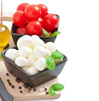 Свежий салат с помидорами черри, базиликом, моцареллой и маслинами.