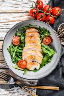 鶏胸肉、ルッコラ、トマトのサラダ。白色の背景。上面図。コピースペース