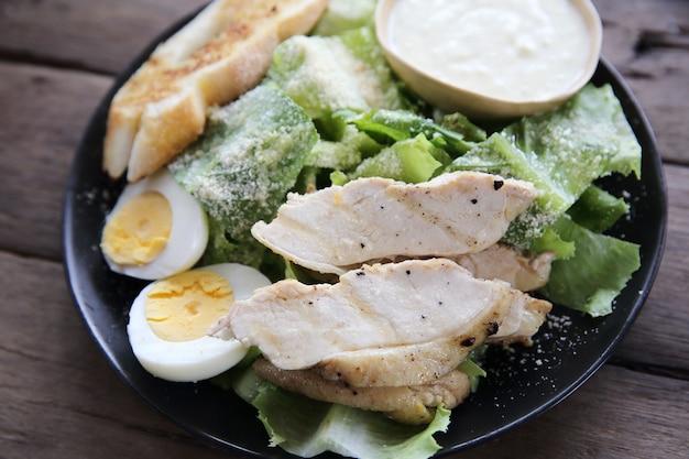 木の背景に鶏の胸肉と新鮮なサラダ