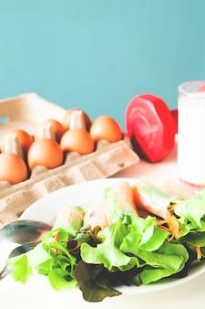 新鮮な卵と牛のサラダ、赤いダンベルのヘルシーメニュー、健康的なライフスタイルのコンセプト
