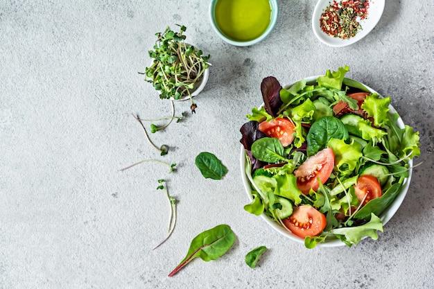 그릇에 신선한 야채 잘 익은 토마토 오이 양상추와 마이크로그린을 곁들인 신선한 샐러드