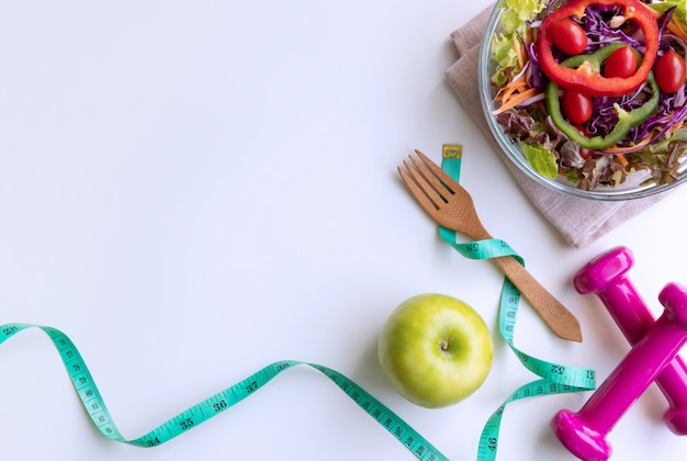 Fresh salad with green apple, dumbbell and measuring tape on white background.