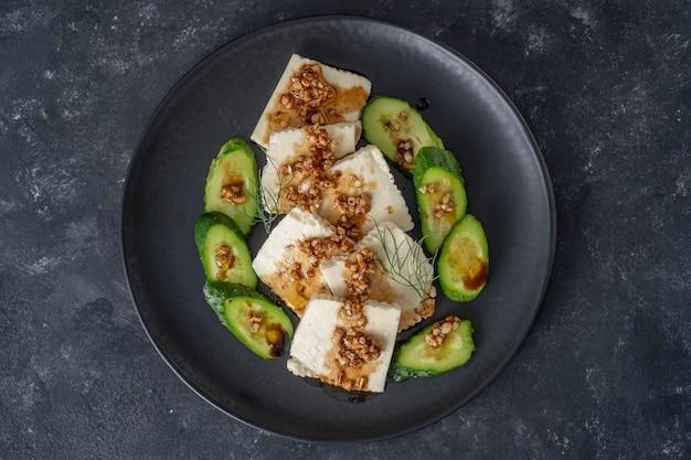 검은 접시에 올리브 오일 소스와 구운 아몬드를 곁들인 녹색 오이와 흰색 치즈를 곁들인 신선한 샐러드, 위쪽 전망, 클로즈업