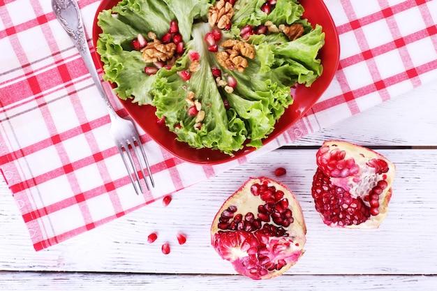 Свежий салат с зеленью, гранатом и специями на тарелке на столе