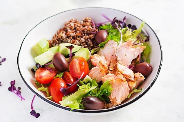 Свежий салат с лососем на гриле, авокадо, помидорами черри, листьями салата, киноа, оливками и микрозеленью