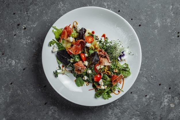 ダークグレーの背景にハムと洋ナシのフレッシュサラダ。ハモンサラダ、サラダミックス、ほうれん草、洋ナシ、ミニトマト