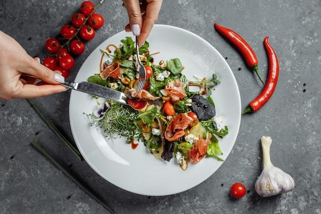 ダークグレーにハムと洋ナシのフレッシュサラダ。ハモンサラダ、サラダミックス、ほうれん草、洋ナシ、チェリートマト、ドーブルー、ケッパー、酢ドレッシングビアンコ。女性の手はフォークとナイフを持っています。