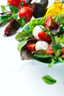 明るい背景のセラミックマグカップにレタス、クレスサラダ、ルッコラ、ビート、トマト、マザレラチーズ、オリーブを添えたフレッシュサラダ。健康食品 。