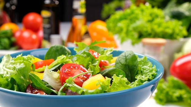Fresh salad with lettuce leaves and tomato in bowl served with healthy food ingredients