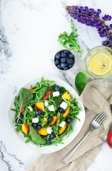 Fresh salad with nectarines blueberries arugula spinach and feta cheese