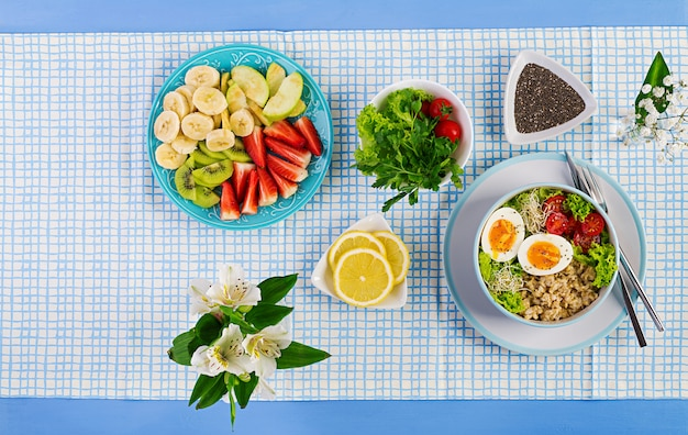 Fresh salad with oatmeal, tomatoes, lettuce, microgreens and boiled egg and fruit plate