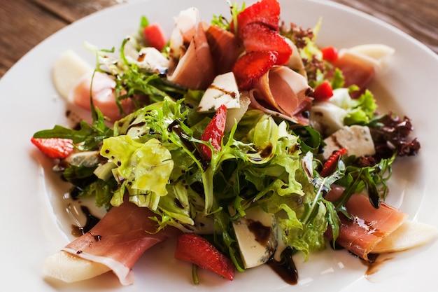 파르마 햄, 블루 치즈 및 딸기가 레스토랑에서 제공되는 신선한 샐러드.