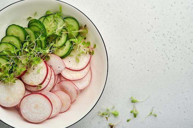 Свежий салат с красной редькой, огурцом, овощами, микрозелеными редисами в белой тарелке