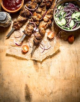 シシカバブの串焼きフレッシュサラダ。木製のテーブルの上。