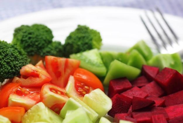 Свежий салат с серебряной вилкой на белой миске