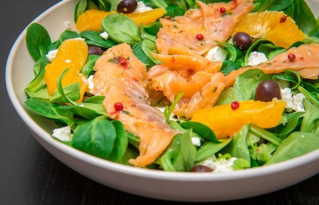 절인 연어와 오렌지 과일 슬라이스를 곁들인 신선한 샐러드
