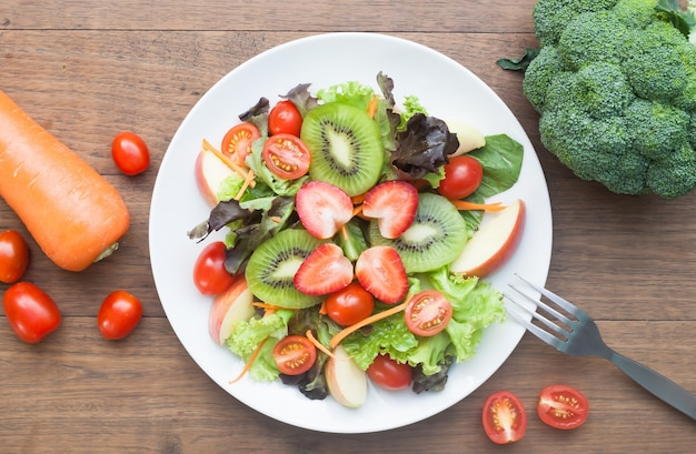 Fresh salad with strawberries, kiwi, tomatoes and apples, top view