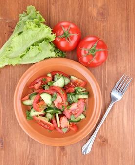 木製の表面にトマトとキュウリのフレッシュサラダ