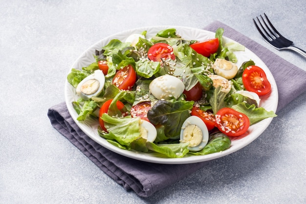 Fresh salad with tomatoes and quail eggs and lettuce.