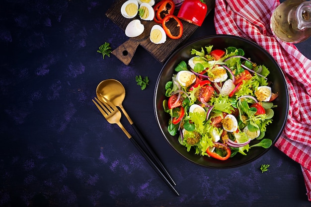 野菜トマト、赤玉ねぎ、レタス、ウズラの卵のフレッシュサラダ。健康食品とダイエットの概念。ベジタリアンフード。上面図、オーバーヘッド