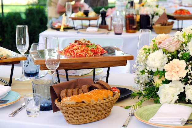 Fresh salad on a wooden plate on a banquet table decorated with elegant floral bouquet.