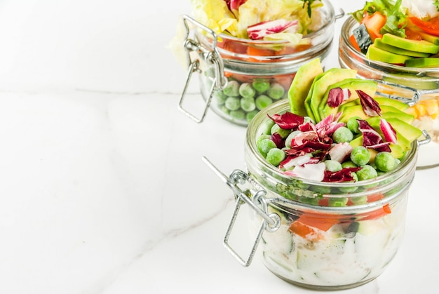 Fresh salads in jar with fresh vegetables and healthy dressings,  on white marble table,  copyspace