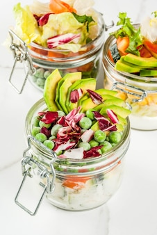Fresh salads in jar with fresh vegetables and healthy dressings on white marble table