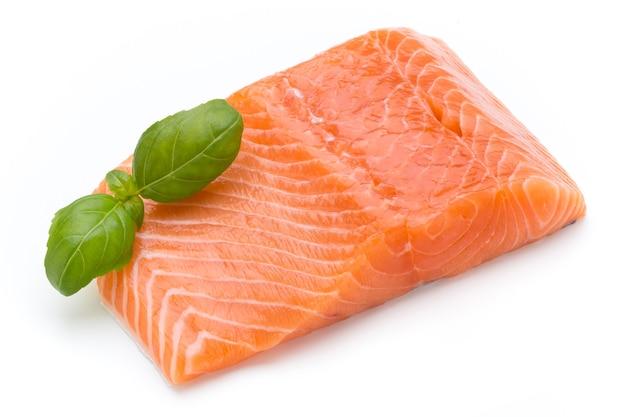 Филе свежего лосося с кусочками на белой поверхности.