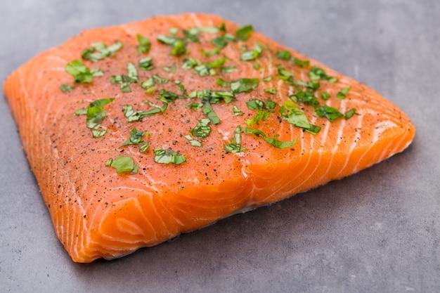 Филе свежего лосося со специями на сером фоне.