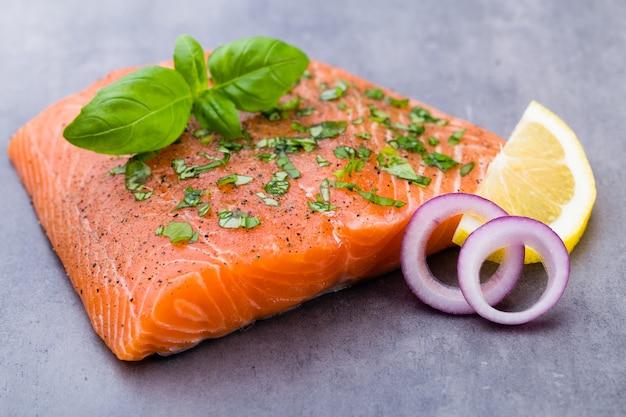Филе свежего лосося со специями на серой поверхности.