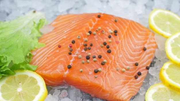 Свежее филе лосося на льду с салатом и долькой лимона