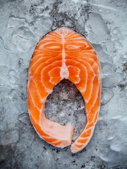 Fresh salmon fillet sliced flat lay on shabby metal background.