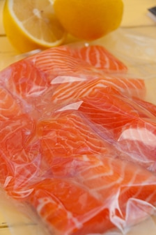 Fresh salmon fillet in a vacuum package with lemon