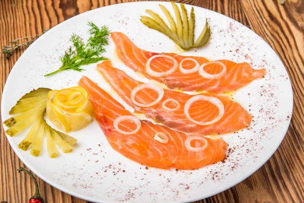 Fresh salmon fillet with aromatic herbs, spices, pink salt and lemon.
